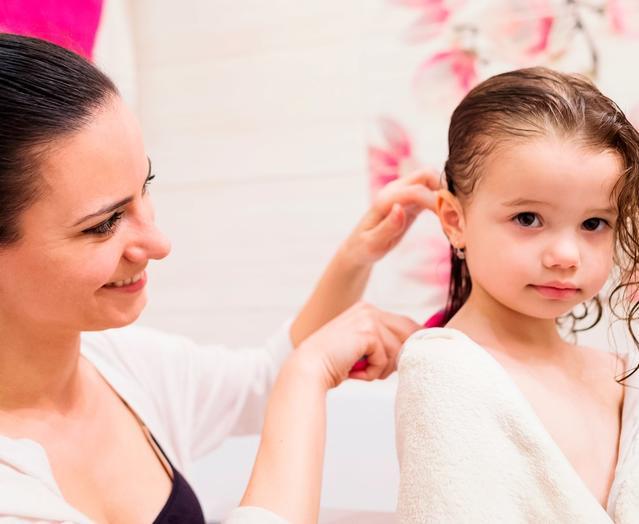 Мама причесывает дочку после мытья головы