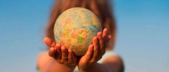 Ребенок держит глобус в руках