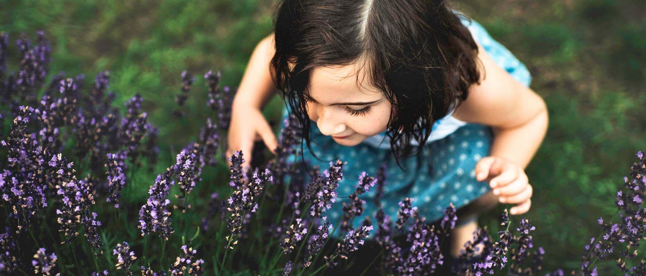 Ребенок, вдыхающий аромат цветов